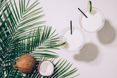 top view of organic coconuts, green palm leaves and coconut cocktails in glasses with drinking straws on white