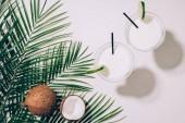 """Постер, картина, фотообои """"вид сверху органических кокосы, листья зеленые пальмы и кокосового коктейлей в очках с трубочки на белом"""""""