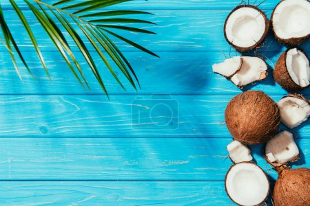 top view of organic healthy coconuts and green palm leaves on blue wooden surface
