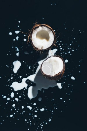 top view of halved organic coconut and coconut milk on black