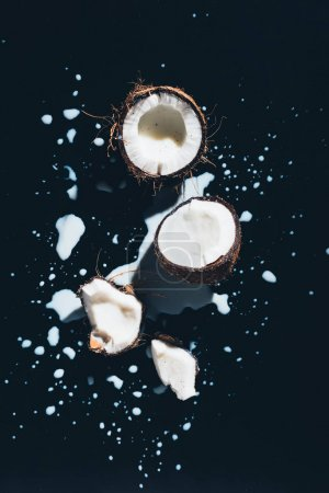 top view of coconut and fresh healthy coconut milk on black