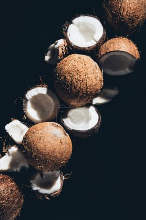 top view of whole and cracked organic coconuts isolated on black