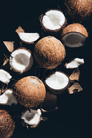 top view of whole and cracked coconuts isolated on black