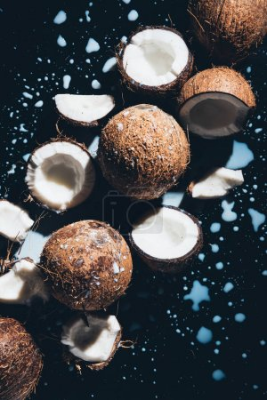 top view of coconuts and fresh tasty coconut milk on black