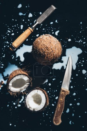 top view of coconuts, chisel, knife and coconut milk on black