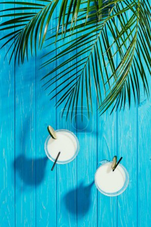 top view of coconut cocktails in glasses and green palm leaves on turquoise wooden table top