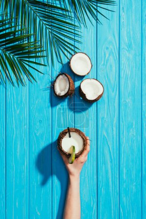 Photo for Top view of human hand with coconut cocktail, cracked coconuts and palm leaves on turquoise wooden surface - Royalty Free Image