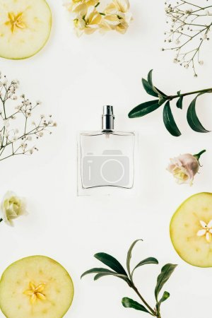 top view of bottle of perfume surrounded with flowers and apple slices isolated on white