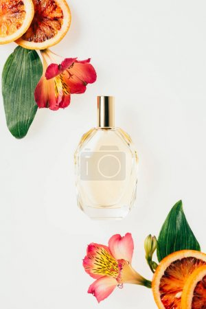 Photo for Top view of bottle of aromatic perfume with flowers and grapefruit slices isolated on white - Royalty Free Image