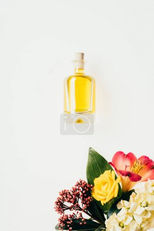 top view of bottle of perfume with colorful flowers isolated on white