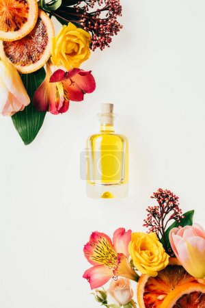 Photo for Top view of bottle of aromatic perfume with beautiful flowers and grapefruit slices isolated on white - Royalty Free Image
