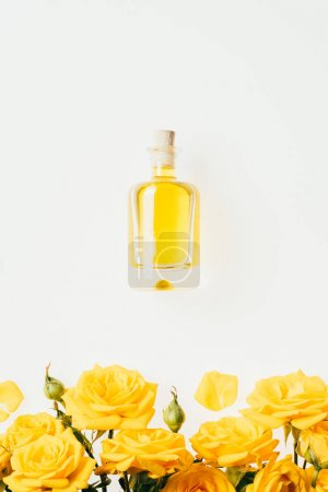 top view of bottle of perfume and yellow roses isolated on white