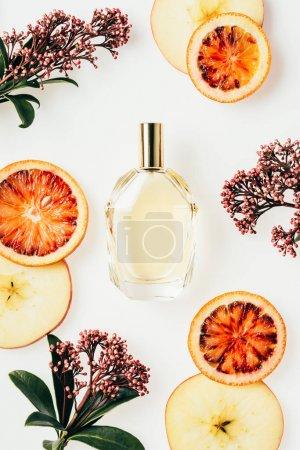Photo pour Vue du dessus du flacon de parfum en verre entouré de fruits et de fleurs isolés sur blanc - image libre de droit
