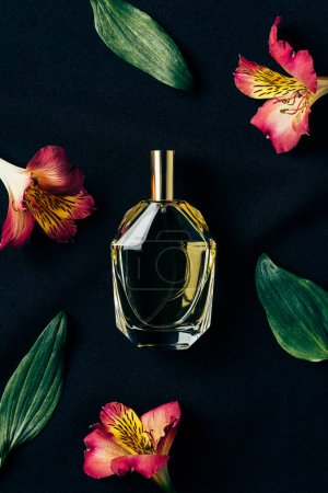 top view of bottle of perfume surrounded with alstroemeria flowers and leaves on black