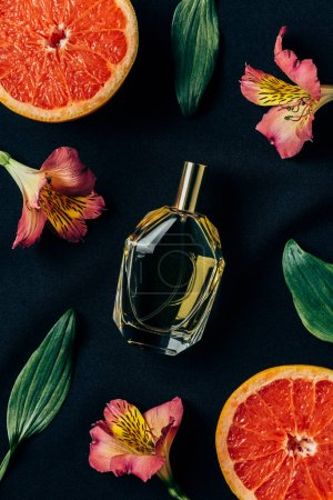 top view of bottle of perfume surrounded with alstroemeria flowers and grapefruit slices on black