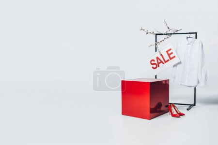 red cube, shirt on hanger and sale sign, summer sale concept