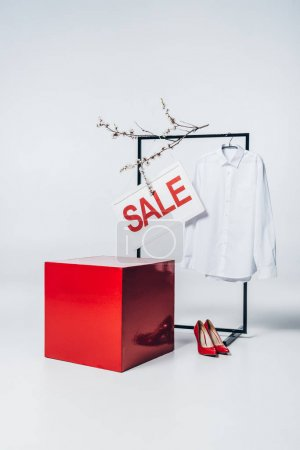 red cube, high heels, shirt on hanger and sale sign, summer sale concept