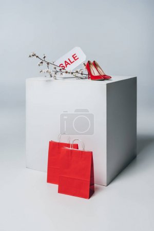 red high heels with sale sign on white cube, summer sale concept