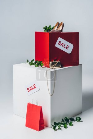 twigs with green leaves and sale signs on cubes, summer sale concept