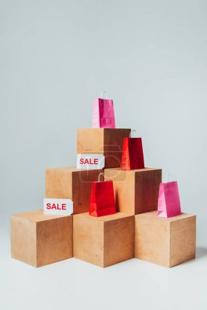 red and pink shopping bags with sale signs on wooden cubes, summer sale concept