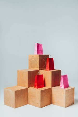 red and pink shopping bags on wooden cubes, summer sale concept