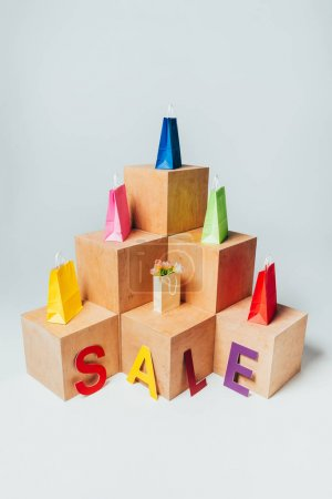 high angle view of colored shopping bags on wooden stands with sale sign, summer sale concept