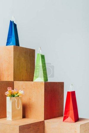 Photo pour Sacs en papier coloré et des tulipes sur des stands en bois isolés sur blanc, concept de vente d'été - image libre de droit