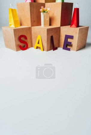 colored paper bags on wooden stands with sale sign, summer sale concept