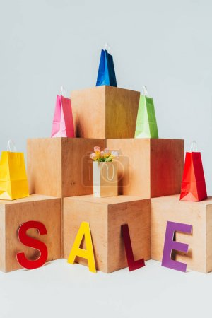 colored shopping bags on wooden stands with sale sign, summer sale concept