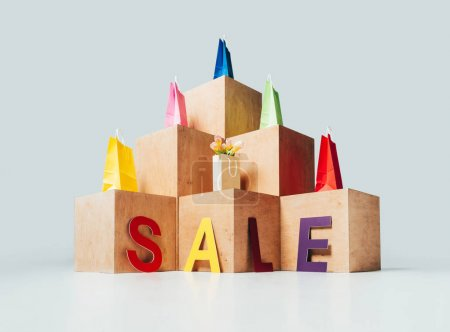 bottom view of colored shopping bags on wooden stands with sale sign, summer sale concept
