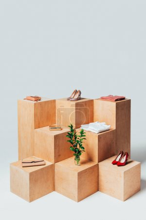 high angle view of high heels and twigs in vase on wooden stands, summer sale concept