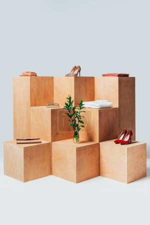 high heels and twigs in vase on wooden stands, summer sale concept