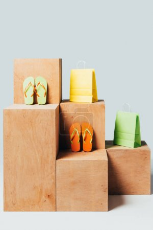 colored paper bags and flip flops on wooden stands, summer sale concept
