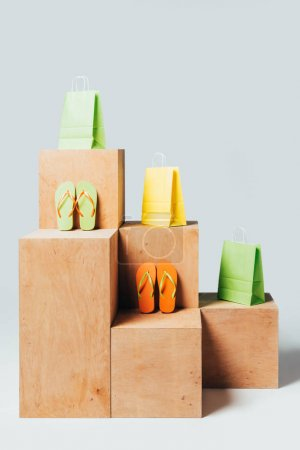 colored shopping bags and flip flops on wooden stands, summer sale concept