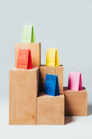 colored shopping bags on wooden stands, summer sale concept