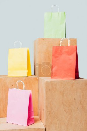colored shopping bags on wooden stands isolated on white, summer sale concept
