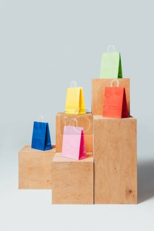 blue, yellow and green shopping bags on wooden stands, summer sale concept