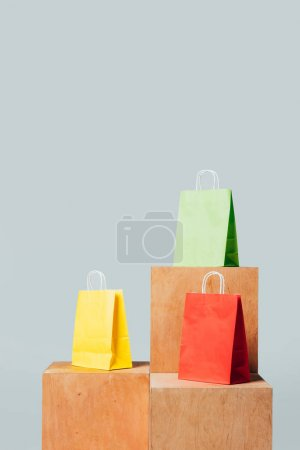 three colored shopping bags on wooden stands isolated on white, summer sale concept
