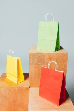 three colored shopping bags on wooden stands, summer sale concept