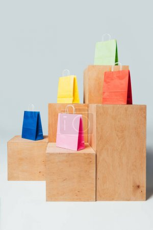 colored paper bags on wooden stands, summer sale concept