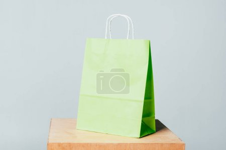 one light green shopping bag on wooden stand isolated on white, summer sale concept