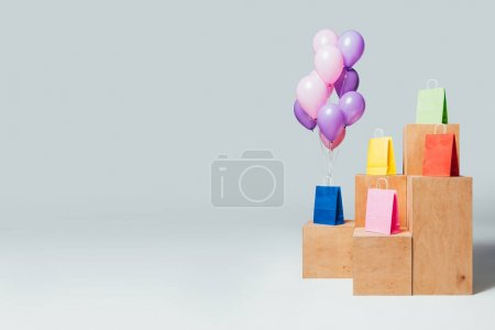 bundle of balloons near shopping bags on stands, summer sale concept
