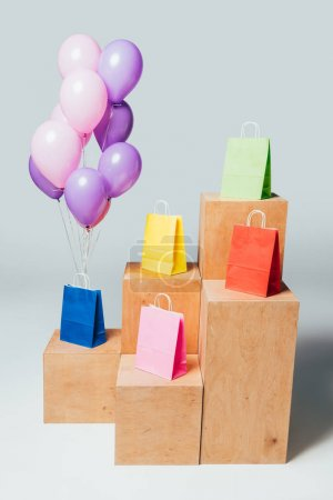 bundle of pink and violet balloons near colored shopping bags on stands, summer sale concept