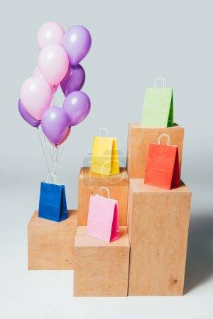 Photo pour Bundle de ballons roses et violettes près de sacs colorés sur les stands, concept de vente d'été - image libre de droit