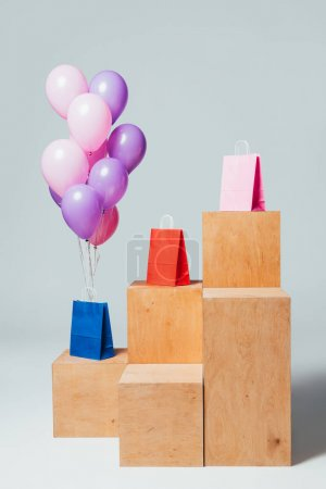 bundle of pink and violet balloons near paper bags on stands, summer sale concept