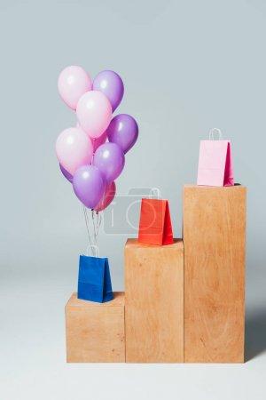 Photo pour Paquet de ballons roses et violets près des sacs à provisions sur les stands, concept de vente d'été - image libre de droit