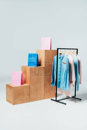 wooden stands with shopping bags and stand with clothes on white, summer sale concept