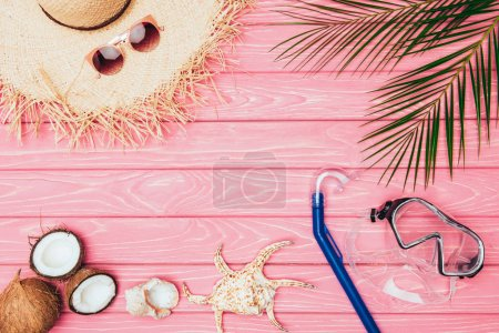 Photo for Top view of different travel attributes on pink wooden surface - Royalty Free Image