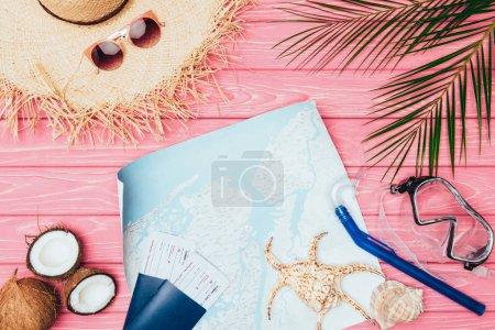Photo pour Vue du dessus de la carte et des billets d'avion entourés de différents attributs de voyage sur une surface en bois rose - image libre de droit