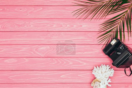 top view of instant print camera with coral and palm leaves on pink wooden surface